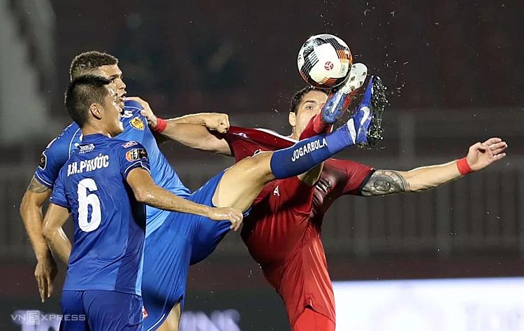TP HCM (áo đỏ) vất vả cầm chân Quảng Nam 1-1 trên sân thống nhất ở giai đoạn 1. Ảnh: Đức Đồng.