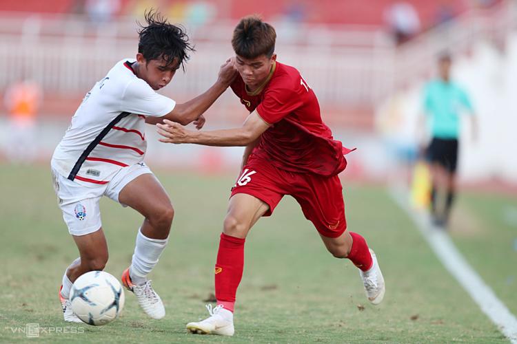 Cầu thủ Việt Nam (đỏ) tranh chấp bóng trong thất bại 1-2 bất ngờ ở lượt cuối cùng bảng B giải U18 Đông Nam Á trên sân Thống Nhất (TP HCM) hôm qua. Ảnh: Đức Đồng.