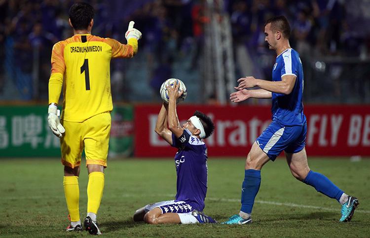 Văn Quyết (ôm bóng) thi đấu với chiếc băng trắng trên đầu trong phần lớn thời gian trên sân. Anh bị đối thủ khiêu khích trước khi đá 11m nhưng vẫn lạnh lùng làm tung lưới Altyn Asyr. Ảnh: Lâm Thỏa.