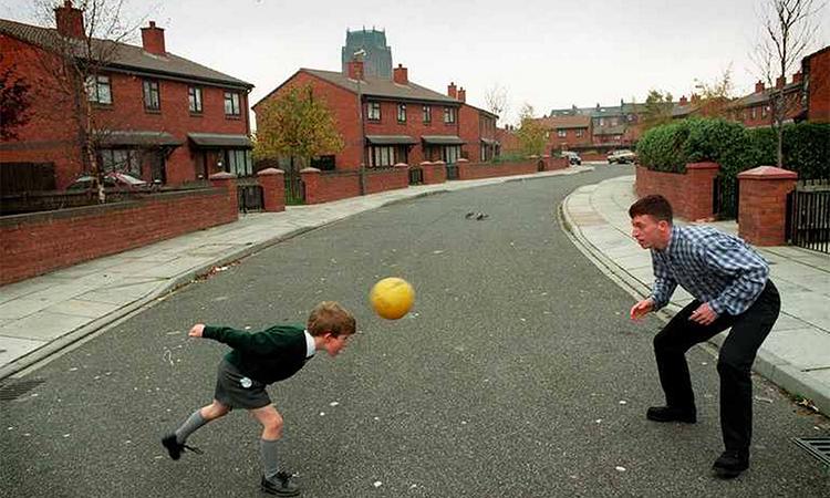 Fowler chơi bóng cùng một bé trai trên đường phố Liverpool, khi anh hãy còn là một cầu thủ trẻ ít được chú ý. Ảnh: Liverpool Echo.