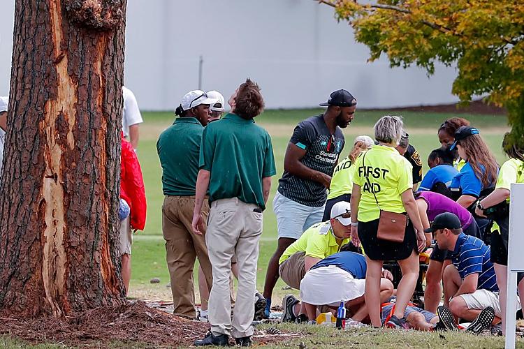 Một cổ động viên được sơ cứu ngay dưới gốc cây hố số 16. Ảnh: New York Times.