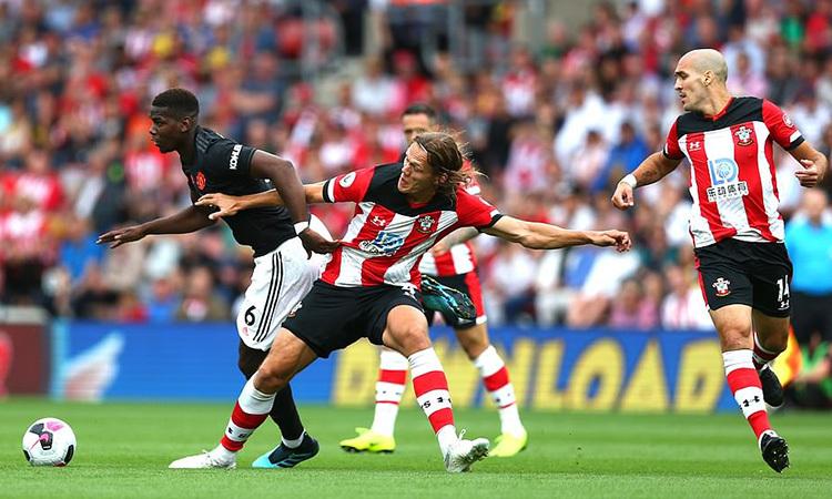 Pogba (trái) đi bóng giữa vòng vây hậu vệ Southampton. Ảnh: AP.