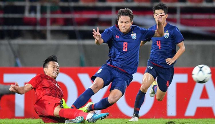 Quế Ngọc Hải tranh chấp với cầu thủ Thái Lan trong trận hoà 0-0 trên sân Thammasat ngày 5/9.