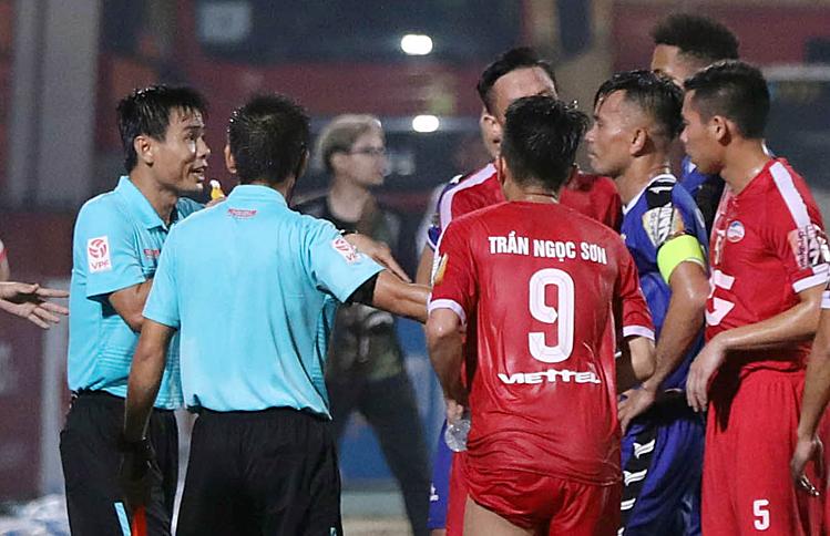 Cầu thủ Bình Dương bao vây phản ứng dữ dội nhưng trọng tài chính Trương Hồng Vũ vẫn bẻ còi không công nhận bàn thắng. Ảnh: Hướng Xuân.