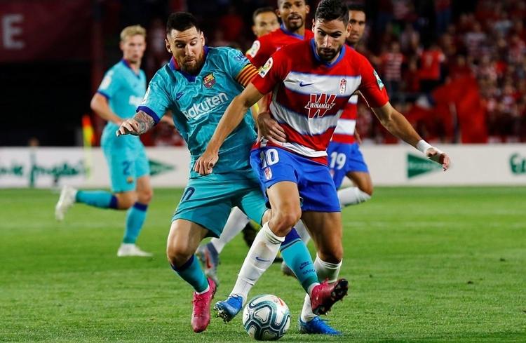 Messi (trái) tranh bóng với cầu thủ Granada trong trận thua cuối tuần trước. Ảnh: Reuters.