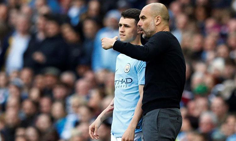 Guardiola (phải) và tài năng trẻ trưởng thành từ lò đào Man City, Phil Foden. Ảnh: Reuters.
