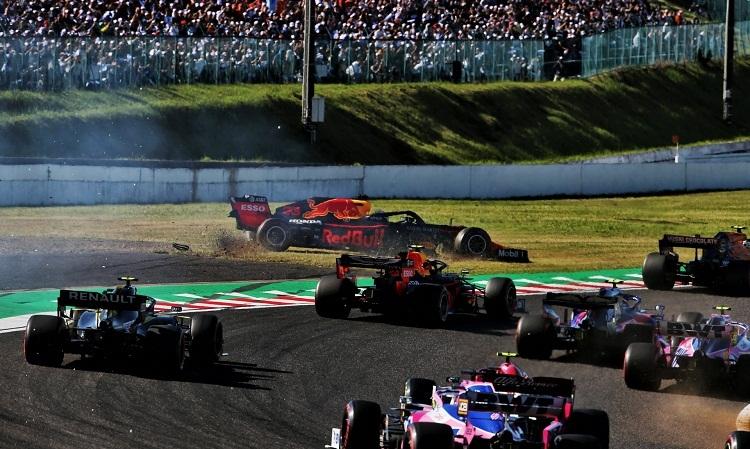 Xe Verstappen bốc khói sau va chạm với Leclerc ở vòng đầu. Ảnh: XPB.