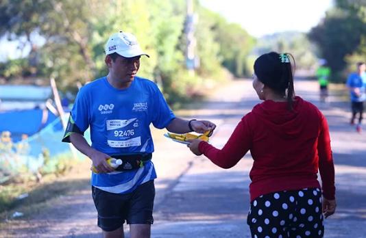 Người dân Quy Nhơn mời vận động viên giải chạy VnExpress Marathon 2019 ăn trái cây trên đường ven hồ Thị Nại.