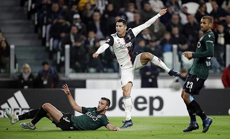 Ronaldo (trắng) khai thông thế bế tắc cho Juventus. Ảnh: AP.