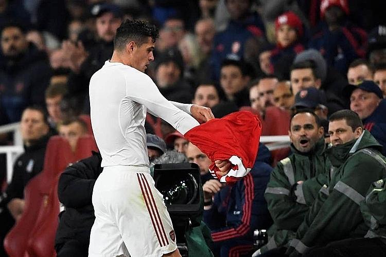 Xhaka vùng vằng cởi áo sau khi rời sân. Ảnh: Reuters.