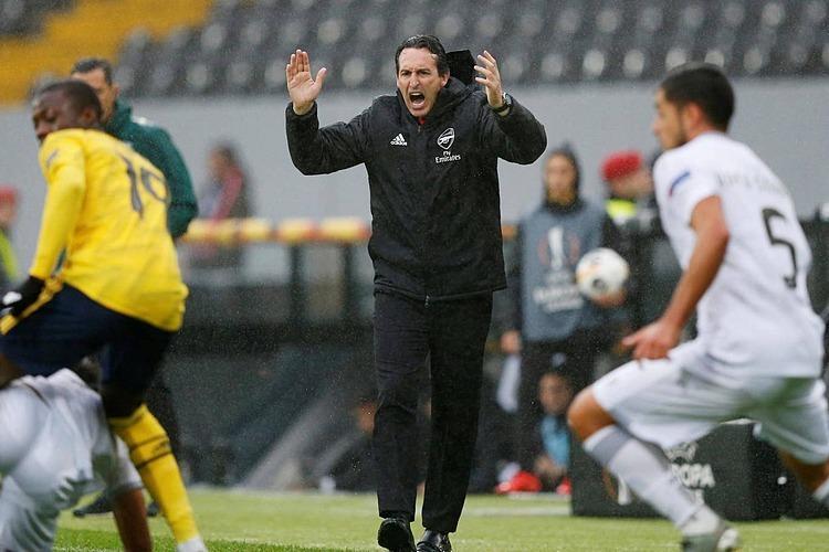 HLV Emery đội mưa chỉ đạo học trò liên tục. Ảnh: Reuters.