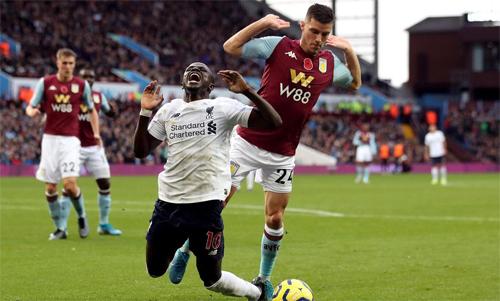 Mane ngã và nhận thẻ vàng trong trận thắng Aston Villa. Ảnh: PA