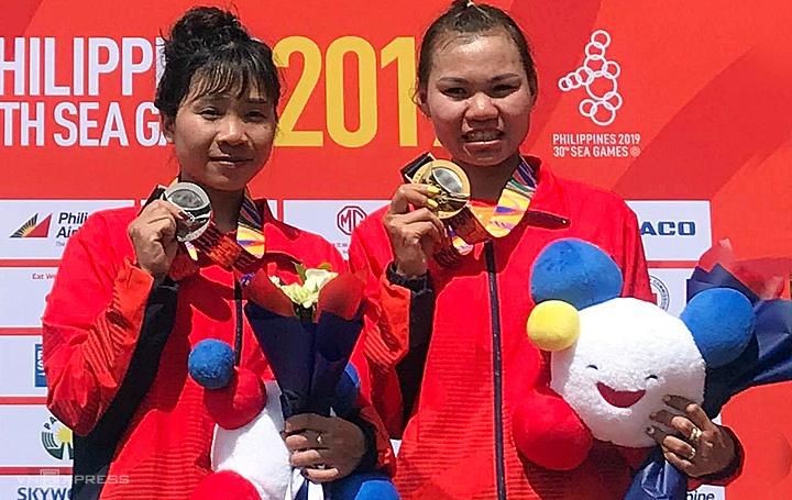 Như Quỳnh (phải) nhận HC vàng bên cạnh đồng đội Cà Thị Thơm nhận HC bạc.