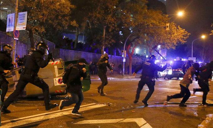 Cảnh sát trấn áp người biểu tình bên ngoài sân của Barca. Ảnh: EFE
