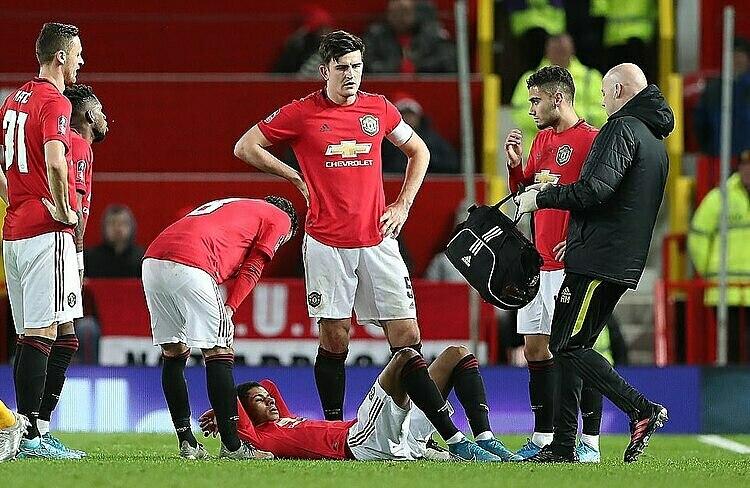 Rashford (nằm) chấn thương lưng chỉ sau 15 phút thi đấu. Ảnh: PA.