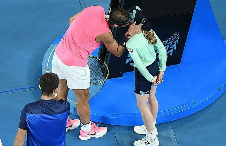 Nadal (hồng) hôn má xin lỗi bé gái nhặt bóng. Ảnh: AFP.