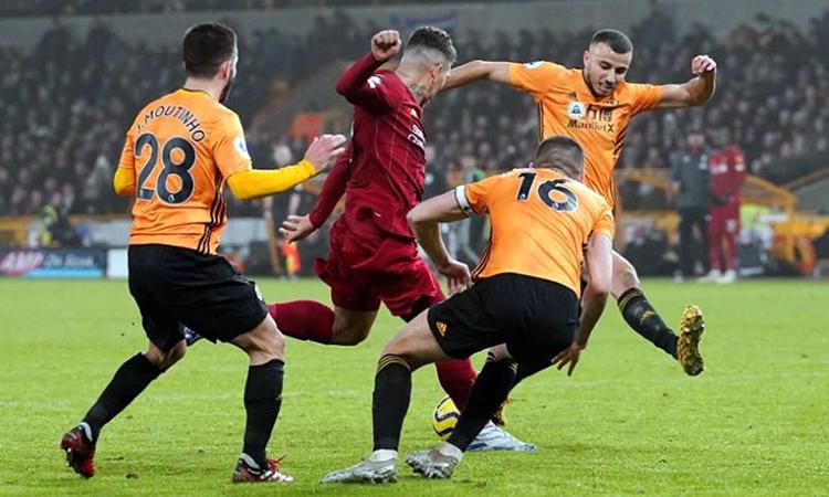 Firmino (áo đỏ) xoay sở giữa vòng vây hàng thủ Wolves. Ảnh: Reuters.