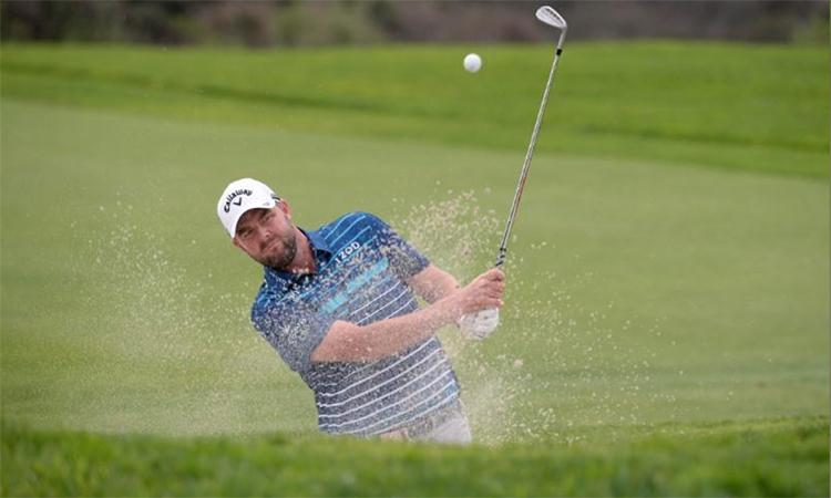 Leishmann đánh bóng khỏi bẫy cát ở hố 17 vòng cuối Farmers Insurance Open hôm 26/1. Ảnh: Reuters.