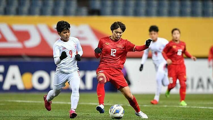 Hải Yến (đỏ) tranh chấp với cầu thủ đối phương.