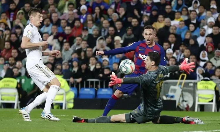 Courtois cứu thua cho Real trong pha đối mặt với Arthur. Ảnh: PA.