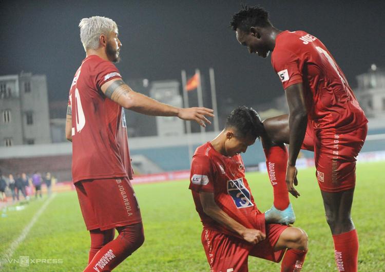 Đồng đội đánh giày cho Mpande sau khi anh ghi bàn gỡ hoà 1-1 trên sân Lạch Tray ngày 13/3. Ảnh: Công Dụng