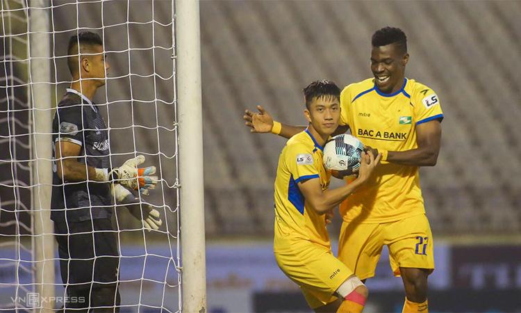 Văn Đức (áo vàng, trái) mừng bàn thắng vào lưới Bình Dương trên sân Vinh chiều14/3. Ảnh: Xuân Thuỷ.