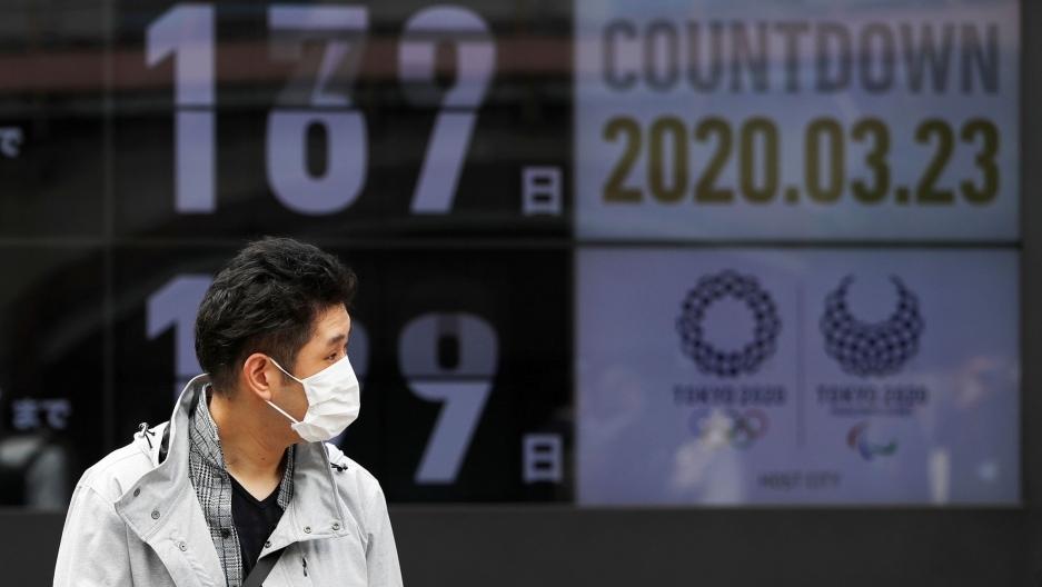 Một người dân đeo khẩu trang, khi đi ngang đồng hồ đếm ngược tới Olympic hôm 23/3. Ảnh: Reuters.