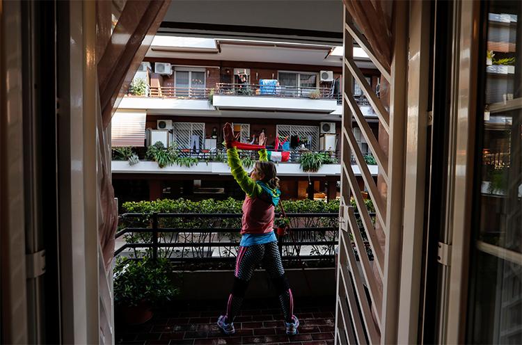 Một HLV thể dục ra ngoài ban-công căn hộ của cô để hướng dẫn cho hàng xóm cùng tập ở Rome hôm 18/3, khi người Italy không thể ra khỏi nhà vì lệnh phong toả toàn quốc. Ảnh: Reuters.