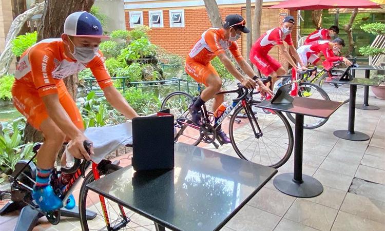 Các cua-rơ đội TP HCM xem đường đua ảo trên iPad trong lúc tập đạp trên rulo. Ảnh: Vinh Ngô.