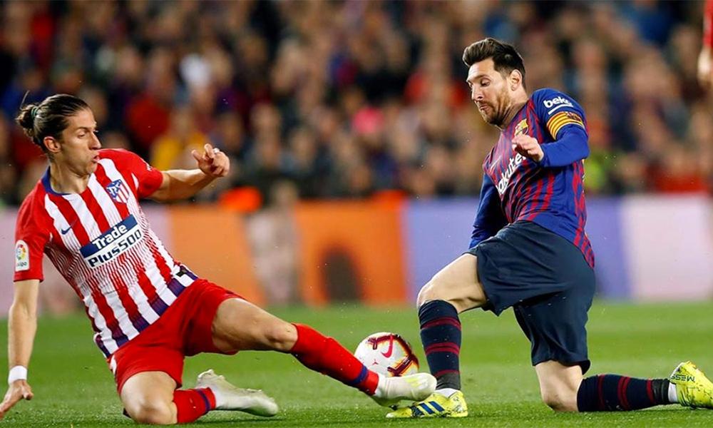 Filipe Luis (trái) nhiều lần phải đá xấu để ngăn cản Messi. Ảnh: EFE.