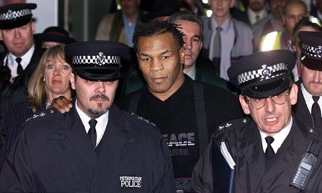 Mike Tyson được cảnh sát hộ tống khi đặt chân đến Anh. Ảnh: AFP.