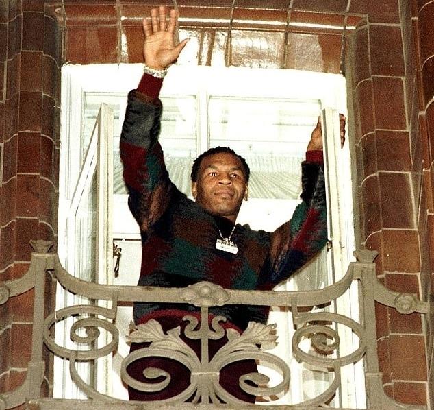 Mike Tyson đứng trên ban công của một khách sạn ở Manchester, vẫy chào người hâm mộ.