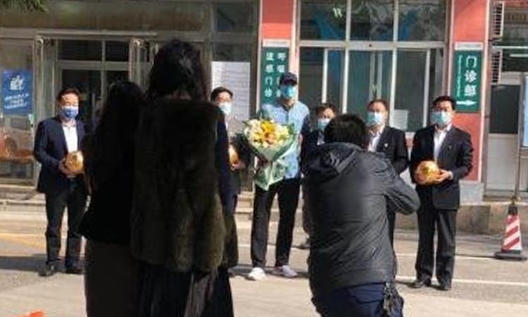Felaini (áo xanh, đội mũ) được tặng hoa và chụp ảnh lưu niệm với các bác sỹ sau khi hoàn thành thời gian điều trị Covid-19. Ảnh: Titan.