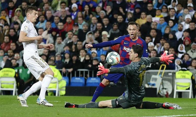 Courtois cản phá pha dứt điểm trong thế đối mặt với Arthur, giúp Real hạ Barca 2-0 tại Bernabeu hôm 2/3/2020. Ảnh: AP.