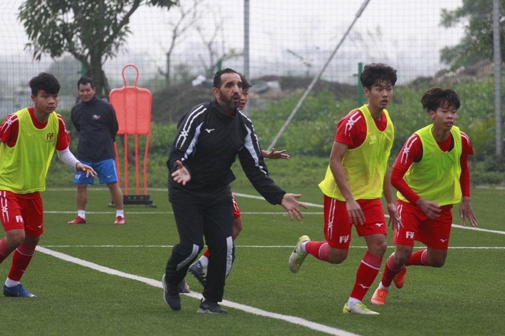 Huấn luyện viên nước ngoài trực tiếp hướng dẫn cầu thủ chơi bóng.