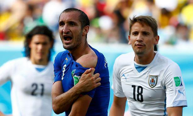 Chiellini (trái) kéo áo, lộ vết răng cắn trước mặt trọng tài. Ảnh: Reuters.