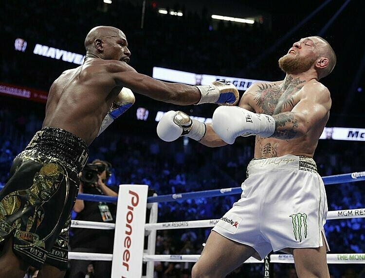 Mayweather (trái) áp đảo McGregor trong trận đấu năm 2017. Ảnh: AP.