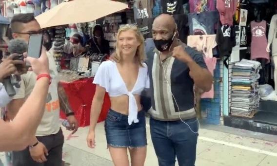 Mike Tyson (phải) đeo khẩu trang, chụp ảnh cùng người hâm mộ. Ảnh: BackGrid.