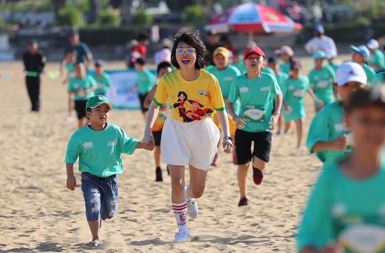Thơ Nguyễn nắm tay một em bé trên đường chạy Kun Kids Marathon.