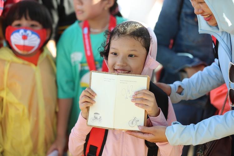 Một em bé hào hứng khi nhận được chữ ký của Thơ Nguyễn.