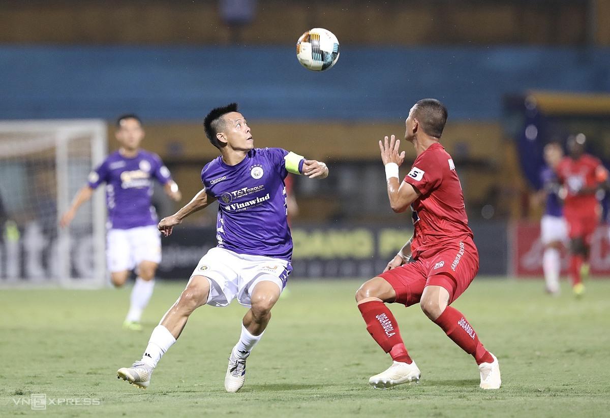 Thủ quân Văn Quyết của Hà Nội (áo tím) tranh chấp bóng với cầu thủ Viettel trên sân Hàng Đẫy. Ảnh: Lâm Thỏa.