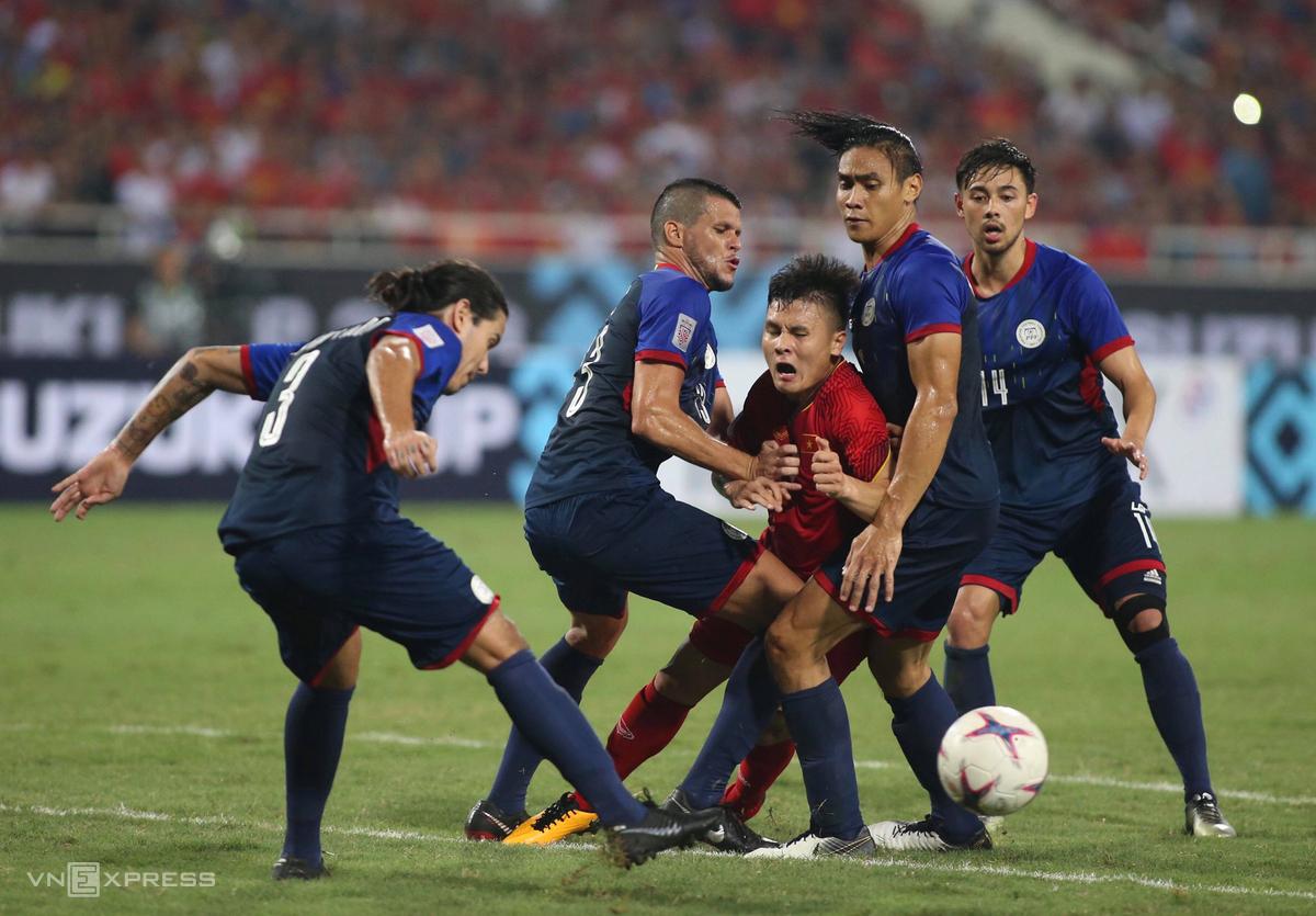 Quang Hải (đỏ) bị các cầu thủ Philippines kìm kẹp trong trận bán kết lượt về AFF Cup 2018 trên sân Mỹ Đình. Ảnh: Lâm Thỏa.