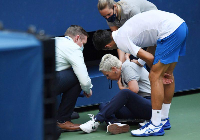 Djokovic (phải) hỏi thăm chấn thương của nữ trọng tài dây. Ảnh: Reuters