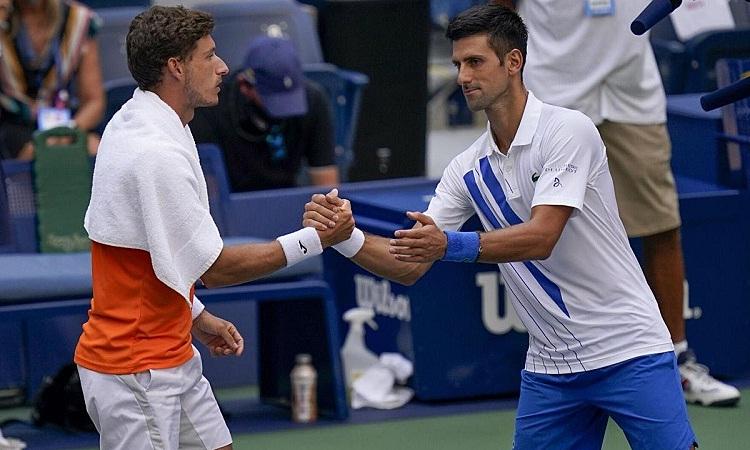 Djokovic bắt tay Carreno Busta sau khi tranh cãi với trọng tài về quyết định loại anh khỏi Mỹ Mở rộng. Ảnh: AP.