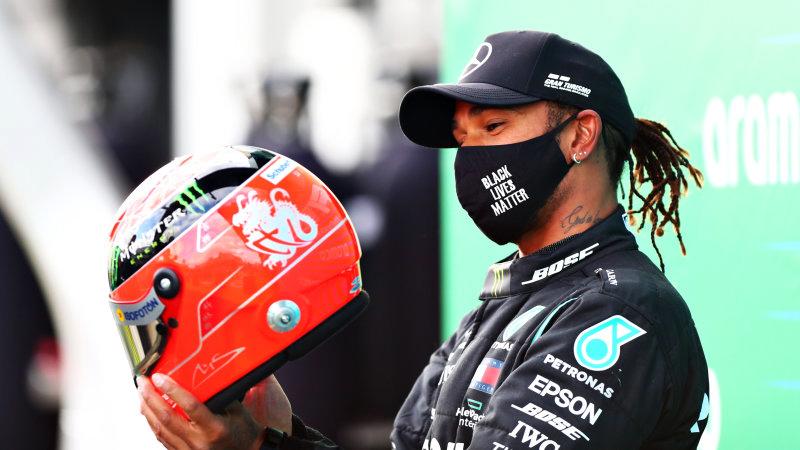 Hamilton ngắm chiếc mũ của Michael Schumcher sau khi được con trai của huyền thoại đàn anh trao tặng.
