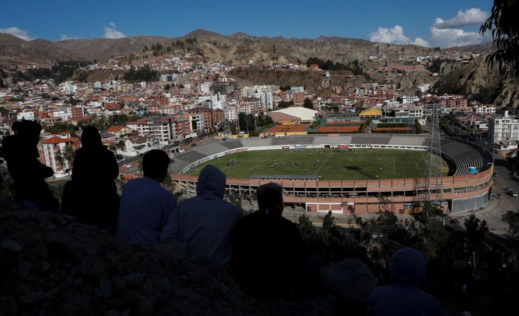 CĐV Bolivia ngồi trên vách núi quan sát buổi tập của tuyển Argentina hôm 12/10. Ảnh: AP