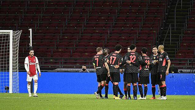 Tagliafico (trái) lầm lũi bước đi sau khi phản lưới. Bên cạnh cầu thủ Liverpool đang mừng bàn thắng. Ảnh: Reuters.