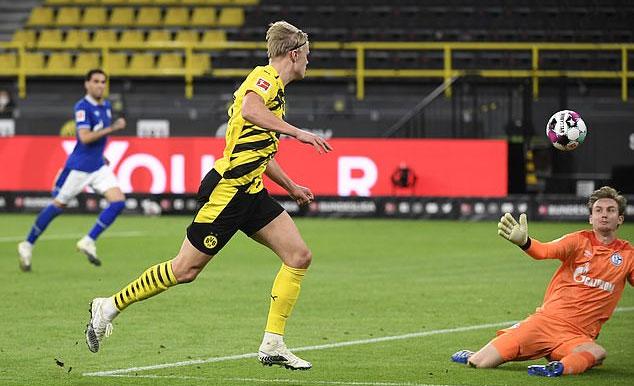 Haaland lốp bóng qua đầu thủ môn Roennow của Schalke. Ảnh: Reuters.