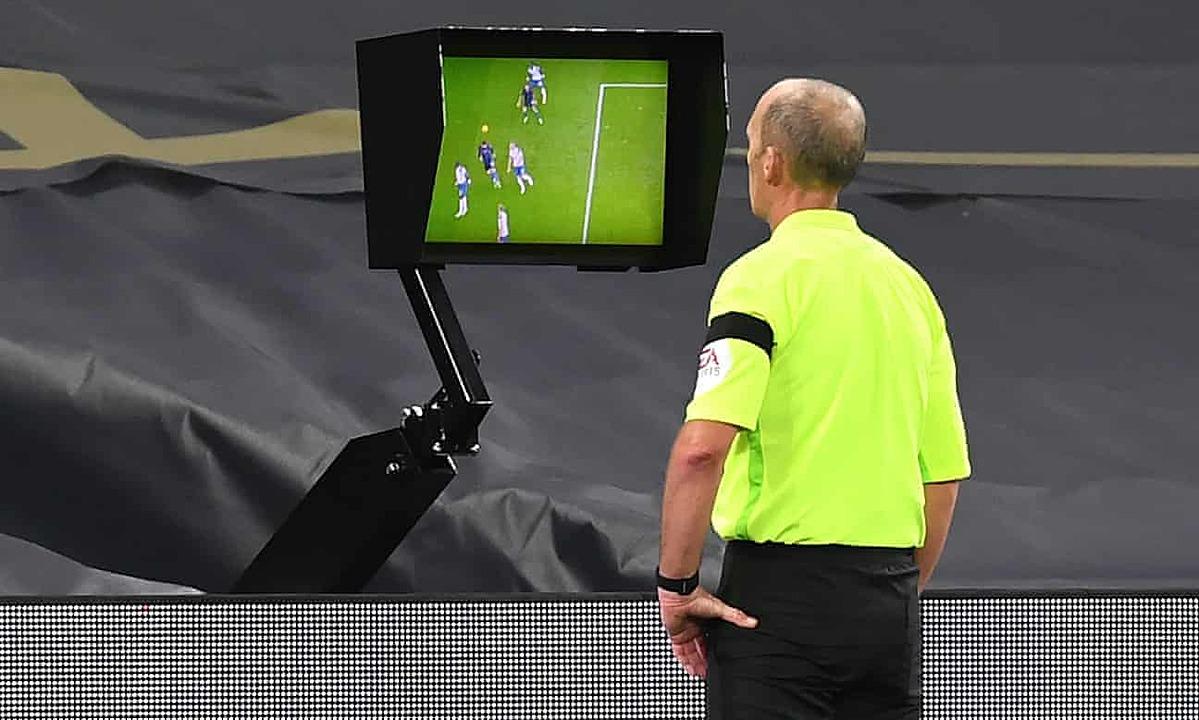 Trọng tài Mike Dean xem lại tình huống Laporte sút tung lưới Tottenham. Ảnh: PA.