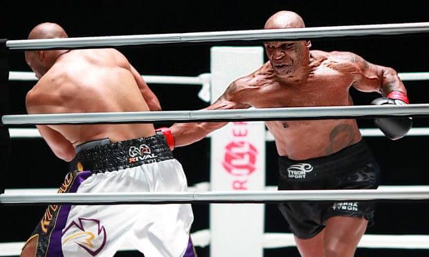Mike Tyson (phải) tung cú thuận tay vào Jones. Ảnh: USA Today Sports.